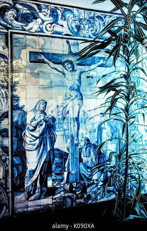 A large religious artwork of blue ceramic tiles (azulejos) depicts Jesus Christ on the cross and decorates an outdoor - Stock Photo