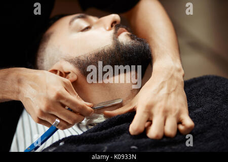 Anonymous man shaving client - Stock Photo