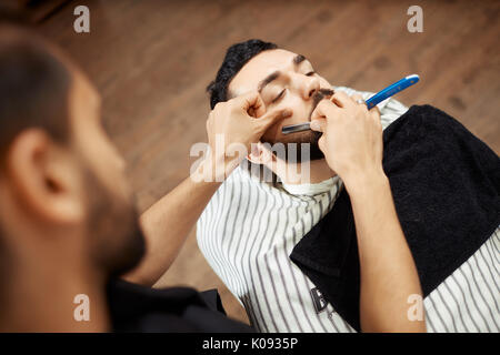 Professional shaving man in chair - Stock Photo