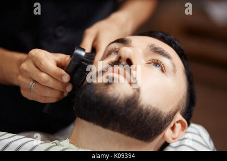 Man grooming client in chair - Stock Photo