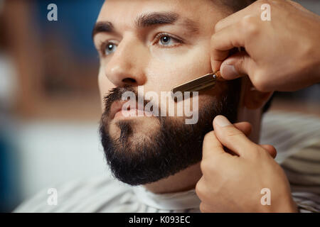 Crop man trimming beard of client - Stock Photo