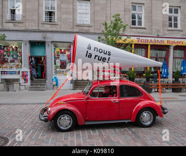 Bright red VW Volkswagen beetle automobile with a large white megaphone attached to its roof, in Old Montreal. - Stock Photo