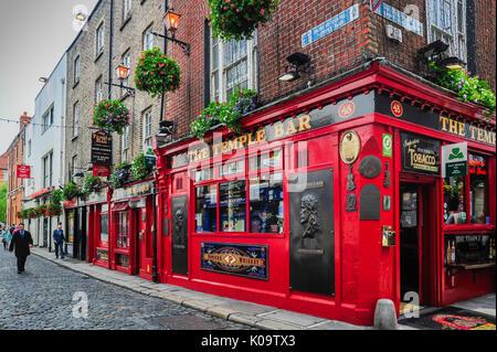 A businessman walks down a cobblestone street near the famous Temple Bar in Dublin, Ireland - Stock Photo