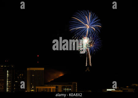 Fireworks light the Tucson sky and light a fire on 'A' Mountain for the 4th of July celebration. - Stock Photo