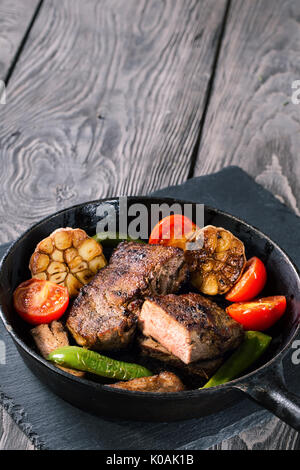 Slightly fried beef steak with vegetables on cast-iron frying pa - Stock Photo