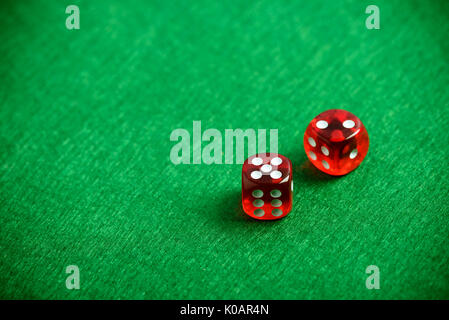 Red poker dices on casino table background - Stock Photo