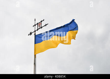 Close up of old Ukranian flag waving on the wind over the hill of Lviv on cloudy day, Ukraine. - Stock Photo