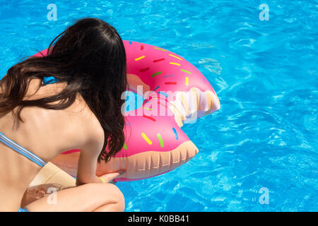 Girl with Inflatable swim ring in shape of donut ready to swim in the pool. Unrecognisable young woman wearing swimsuit - Stock Photo