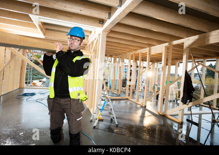 Carpenter In Protective Jacket Carrying Wood On Shoulder At Site - Stock Photo