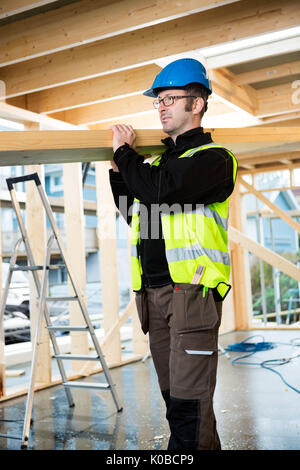 Confident Carpenter Carrying Wood On Shoulder At Site - Stock Photo