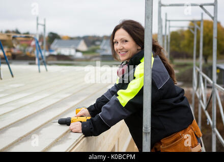 Female Carpenter Smiling While Holding Drill Machine At Roof - Stock Photo
