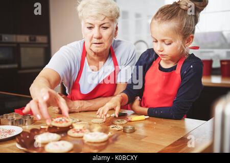 Grandma and granddaughter decorating cookies - Stock Photo