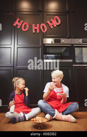Grandma and cute girl eating home made cookies - Stock Photo