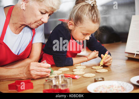 Small girl decorating cookies with her grandma - Stock Photo