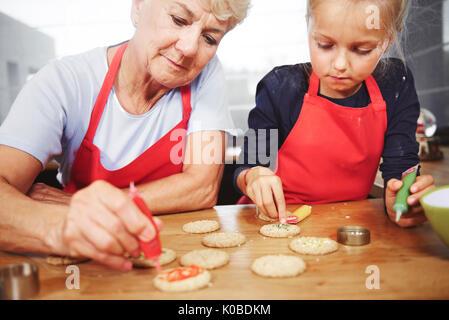 Grandmother with girl decorating christmas cookies - Stock Photo