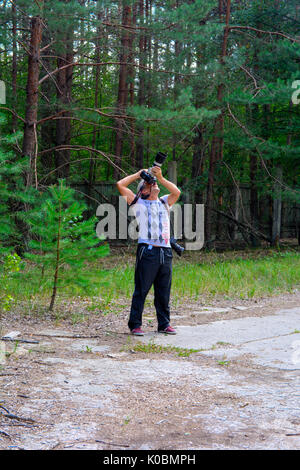 The photographer takes pictures in the exclusion zone. Dead military unit. Consequences of the Chernobyl nuclear - Stock Photo