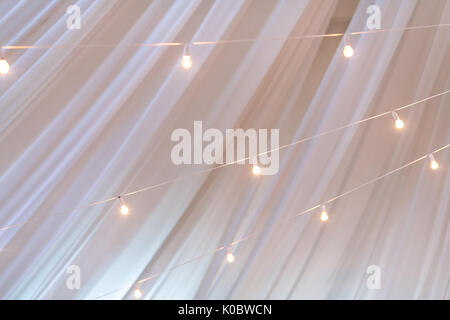 illumination, decoration, celebration concept. against the background of white ghostly transparent curtains there - Stock Photo