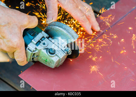 Close-up of worker cutting metal with electric grinder. Sparks while grinding iron - Stock Photo