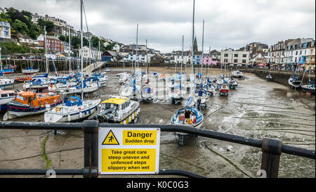 Danger sudden drop warning sign at Ilfracombe harbour, with many moored boats at low tide, and properties overlooking. - Stock Photo