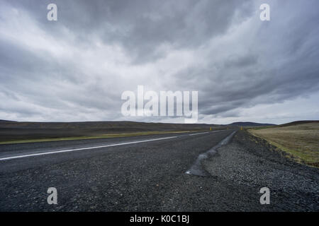 Iceland - Dark road with no end through lava fields Stock Photo