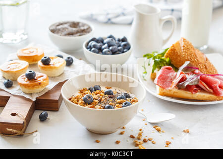 granola with yogurt, sandwiches with meat and avocado, and mini cheesecakes with blueberries for breakfast. - Stock Photo