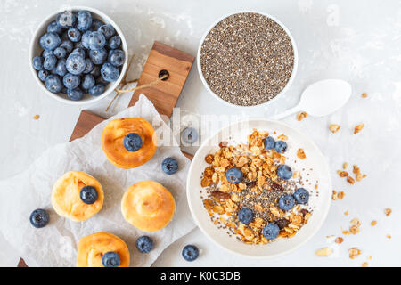 granola with yogurt and mini cheesecakes with blueberries for breakfast. - Stock Photo