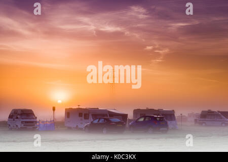 The sun rises over a misty campsite in the UK at dawn on an August morning. - Stock Photo