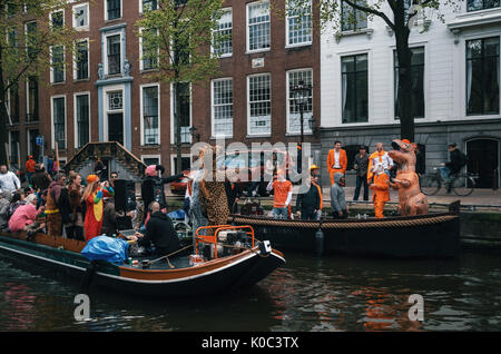 Amsterdam, Netherlands - 27 April, 2017: Local people and tourists dressed in orange clothes and funny costumes - Stock Photo