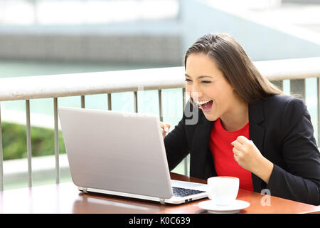 Excited executive reading an on line notification in a laptop sitting in a coffee shop - Stock Photo