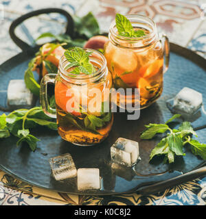 Summer refreshing cold peach ice tea with mint, square crop - Stock Photo