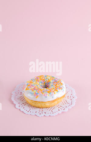 a multicolor donuts presented on a doily paper and a pop colorful background. - Stock Photo