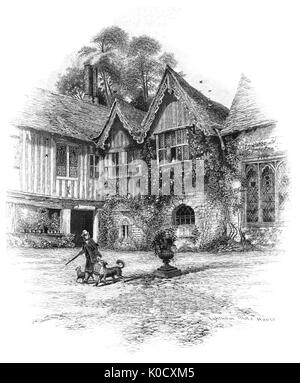1870: A gamekeeper and dogs outside Ightham Mote House dating from circa 1340-1360 is a medieval moated manor house. - Stock Photo