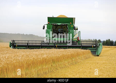 SALO, FINLAND - AUGUST 18, 2017: John Deere Combine T660 with cutting unit 630D harvests barley, the grain tank - Stock Photo