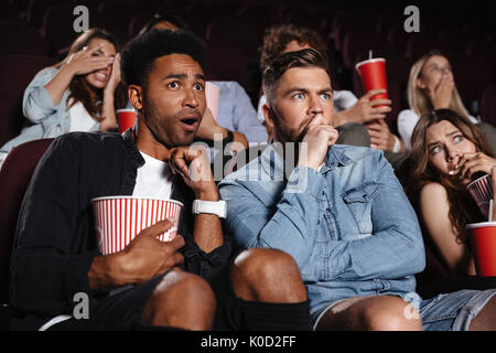 Image of shocked scared young friends sitting in cinema watch film drinking aerated sweet water. - Stock Photo