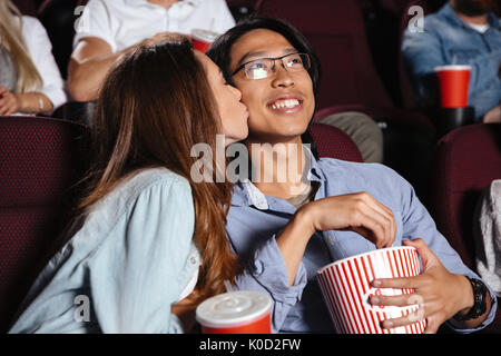 Image of young loving couple sitting in cinema watch film and kissing - Stock Photo
