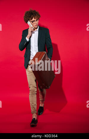 Confident young man in white shirt walking with suitcase while talking on mobile phone isolated over red background - Stock Photo