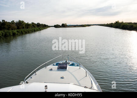 First person point of view over the prow of a cruise boat sailing on a canal approaching a fork in the waterway - Stock Photo