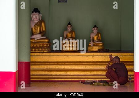Buddhist monk prays in the Setyyanthiha Paya temple, Mandalay, Myanmar - Stock Photo