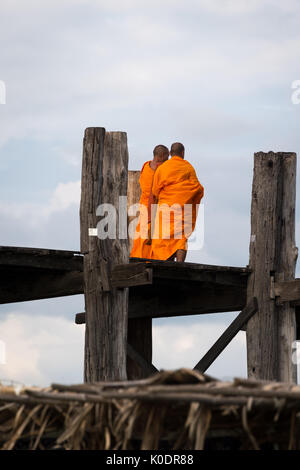 Buddhist monks in conversation as they cross the U Bein bridge, Taungthaman Lake, Mandalay, Myanmar - Stock Photo