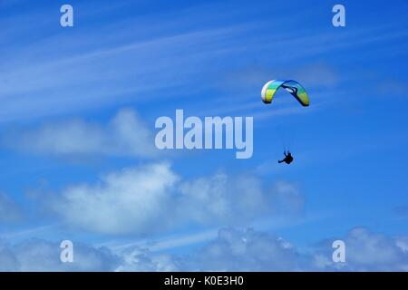 paraglider against blue sky with clouds - Stock Photo