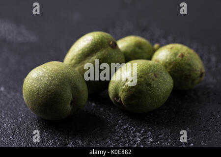 Fresh green walnuts in the skin just from the tree. Walnuts on a black background. Macro. Fresh Harvest. - Stock Photo