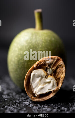 A fresh green walnut in the peel is fresh from the tree. Walnut on a black background. Macro. Fresh Harvest. - Stock Photo