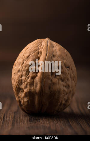 A beautiful large walnut in a shell on a wooden background. Nut and background of one color. Walnuts on a wooden - Stock Photo