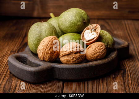 Fresh harvest of walnuts on a wooden background. Green and brown nuts on a beautiful wooden plate. Shell and peel - Stock Photo