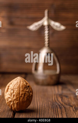 A walnut in a shell on a wooden background together with an old nutcracker. Walnut and beautiful vintage nutcracker. - Stock Photo