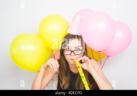 Young woman with party hat with noisemaker on a white background - Stock Photo