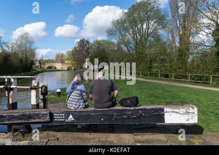 Couple sitting on some lock gates, enjoying the afternoon sunshine; Grand Union Canal, Stoke Bruerne, Northamptonshire, - Stock Photo