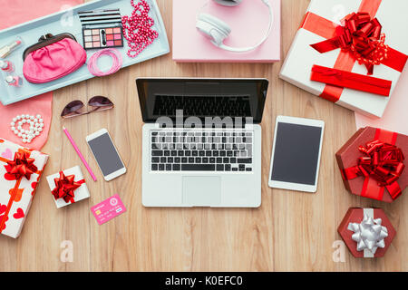 Fashion blogger desktop with laptop, credit card, touch screen mobile devices, gift boxes and beauty accessories, - Stock Photo