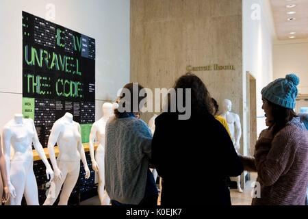 Three students wearing winter clothing huddle in front of a row of white mannequins and a large black poster comprising - Stock Photo