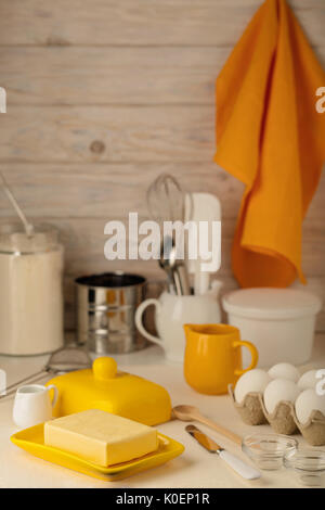 Kitchen utensils, tools and products for homemade cakes on a light wooden background. Selective focus. - Stock Photo